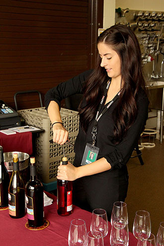 Tayja Owsley, recently hired as the Southern Oregon Wine Institute's beverage captain, serves at the public wine tastings held Friday and Saturday afternoons  in the Danny Lang Center. The $5 tasting fee for sampling five wines is waived with a bottle purchase.