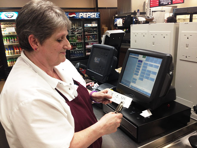 Margaret Davis, cafeteria employee, punches a cafe card for a student.